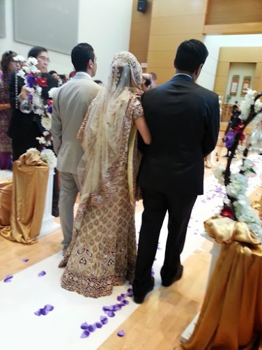 The bride takes her first steps down the aisle towards her husband to be alongside her two brothers.