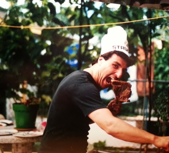 An old photo of my dad cooking BBQ at his in-laws' house, gnawing on a steak. Keepin' it classy!