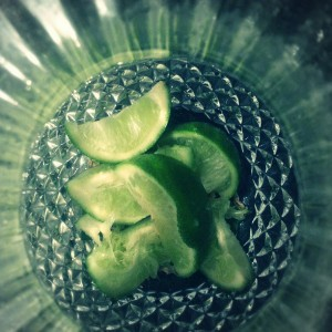 One whole sliced lime in a crystal water pitcher. What this image doesn't allow to the viewer to see is the ginger root and fresh mint leaves hidden underneath the slices of delicious citrus.