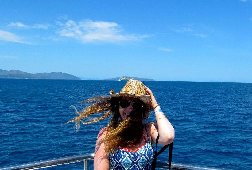 I stand for a windy boat ride photo while making my way out to the Great Barrier Reef. Photo by: Leviana Coccia.