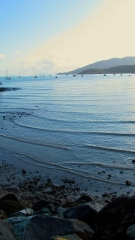 Waves roll in and lightly crash against the rocks which decorate the Airlie Beach shore. Photo by: Leviana Coccia.