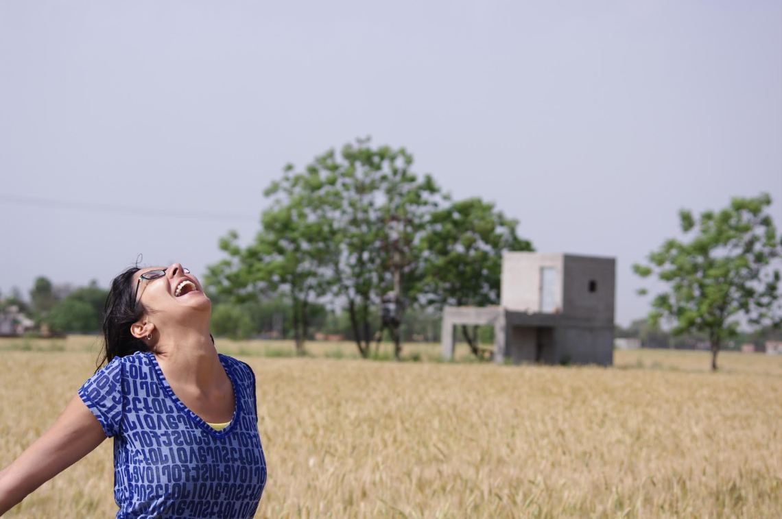 "Kernjeet is standing on the land that belonged to her ancestors but has since been passed down to her father and his brother. Here, they grow and harvest wheat. ""The most soothing calming grounding place in the world for me is the road leading out of my dad's village, Marhana in Punjab, India,"" Kernjeet says. Courtesy of: Kernjeet Sandhu."