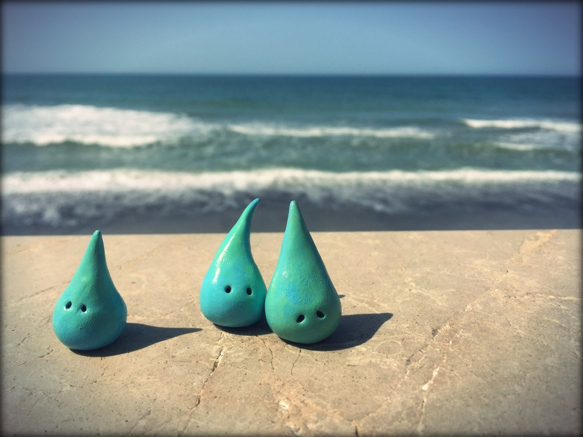 There are three teal 3D tear-drop figurines, about one inch in size, each a unique shape, sitting on a step near the shore of a wavy body of water. This is by Danette Relic.