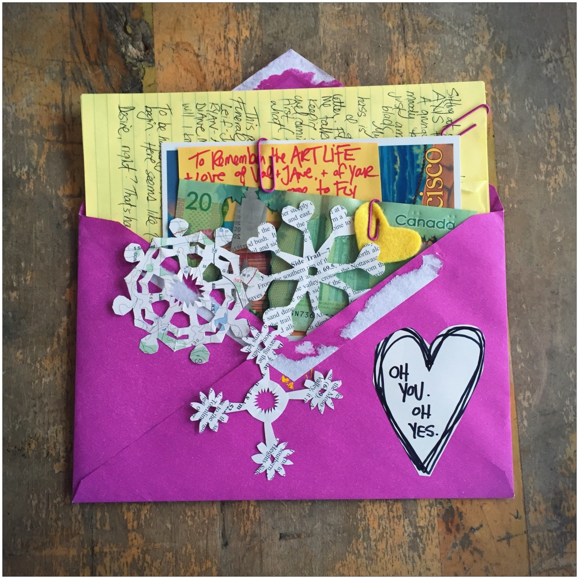 "A purple envelope filled with a birthday letter, written in black ink on a yellow sheet of lined paper. There are some homemade snowflake cut-outs in the foreground as well as a heart cut-out that reads, ""Oh you. Oh yes."" This is by Danette Relic."