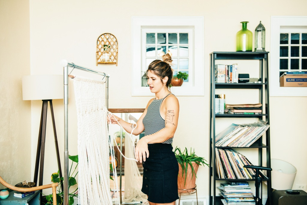 Ashley Burk, Founder and CEO of Steady Hand Creative Co. and IAFTDR, stands in a black denim skirt and a striped tank top, working on a macramé fibre art piece. Photo by: Dani Fresh.