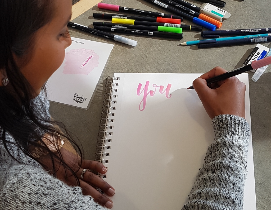 "Usha Rajpal Cheddi beginning to craft the phrase, ""You are strong,"" using soft pink pen ink. Photo courtesy of: Usha Rajpal Cheddi."