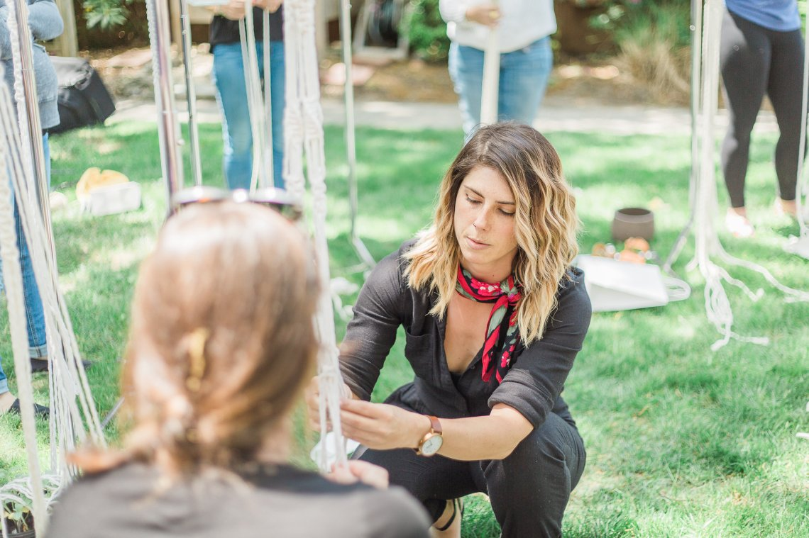 Ashley Burk, Founder and CEO of Steady Hand Creative Co. and IAFTDR, leads a macramé workshop outside in a grassy area, as participants around her create one-of-a-kind plant hangers. She is pictured assisting a guest with their fibre art. Photo by: Megan Khichi.