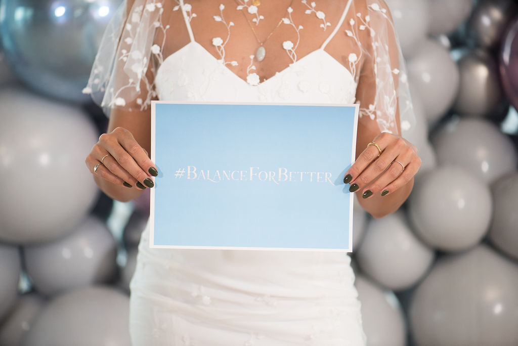 Meghan Yuri Young, Founder of The Sad Collective, at Alicia Jenelle Events' #BalanceforBetter International Women's Day style shoot. Meghan holds a sign that reads, #BALANCEFORBETTER. Photo by: Alicia Campbell Photography.