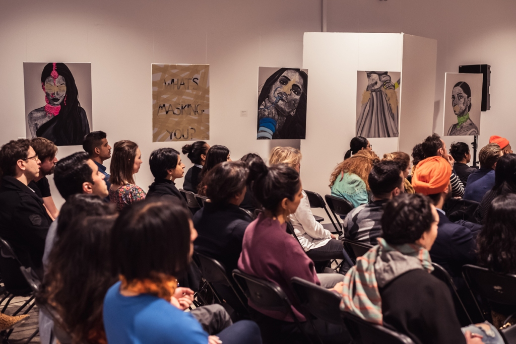"The audience at Romana Kassam's MasksxMolds exhibiition are seated during a presentation. Romana's works are hung in a gallery throughout the room, alongside a print that reads, ""What's masking you?"" Photo by: Nabeel Pervaiz."