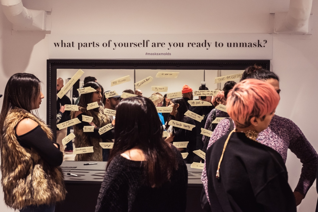 "Four guests gather at Romana Kassam's first solo exhibition, MasksxMolds, looking at answers to the posed question, ""What parts of yourself are you ready to unmask?"" This question is printed above a mirror and the mirror has various answers written on pieces of masking tape, which are stuck to the mirror. Photo by: Nabeel Pervaiz."