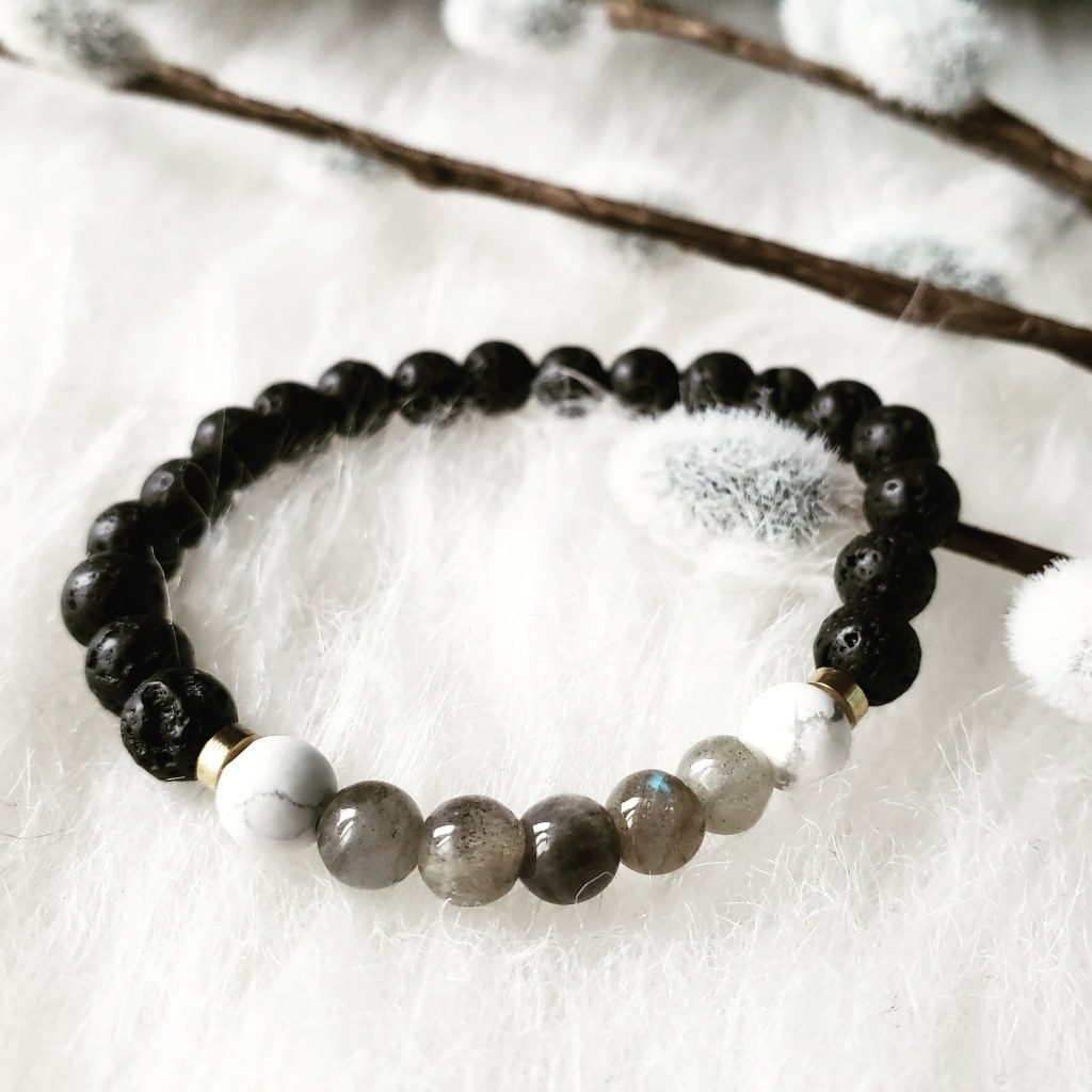 A Howlite and Labradorite stone bracelet by Trias. Photo by; Alvia Giash. Black stones make up most of this bracelet, with marble white and grey stones collecting at the middle, paired with two subtle gold beads. Photo by: Alvia Giash.