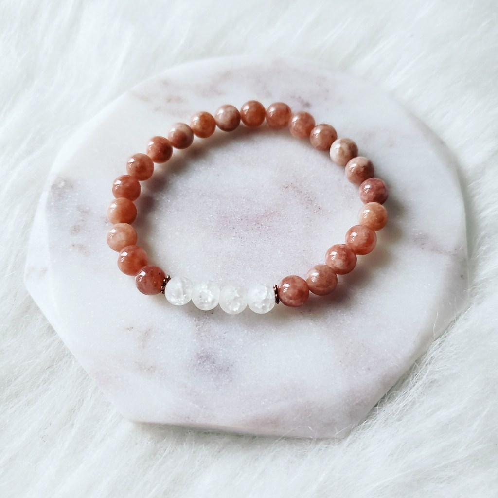 A Mashan Jade and Crackle Rock Quartz bracelet made by Trias. Majority of this bracelet is made with blush coloured stone beads and four white stones are in the middle. Photo by: Alvia Giash.