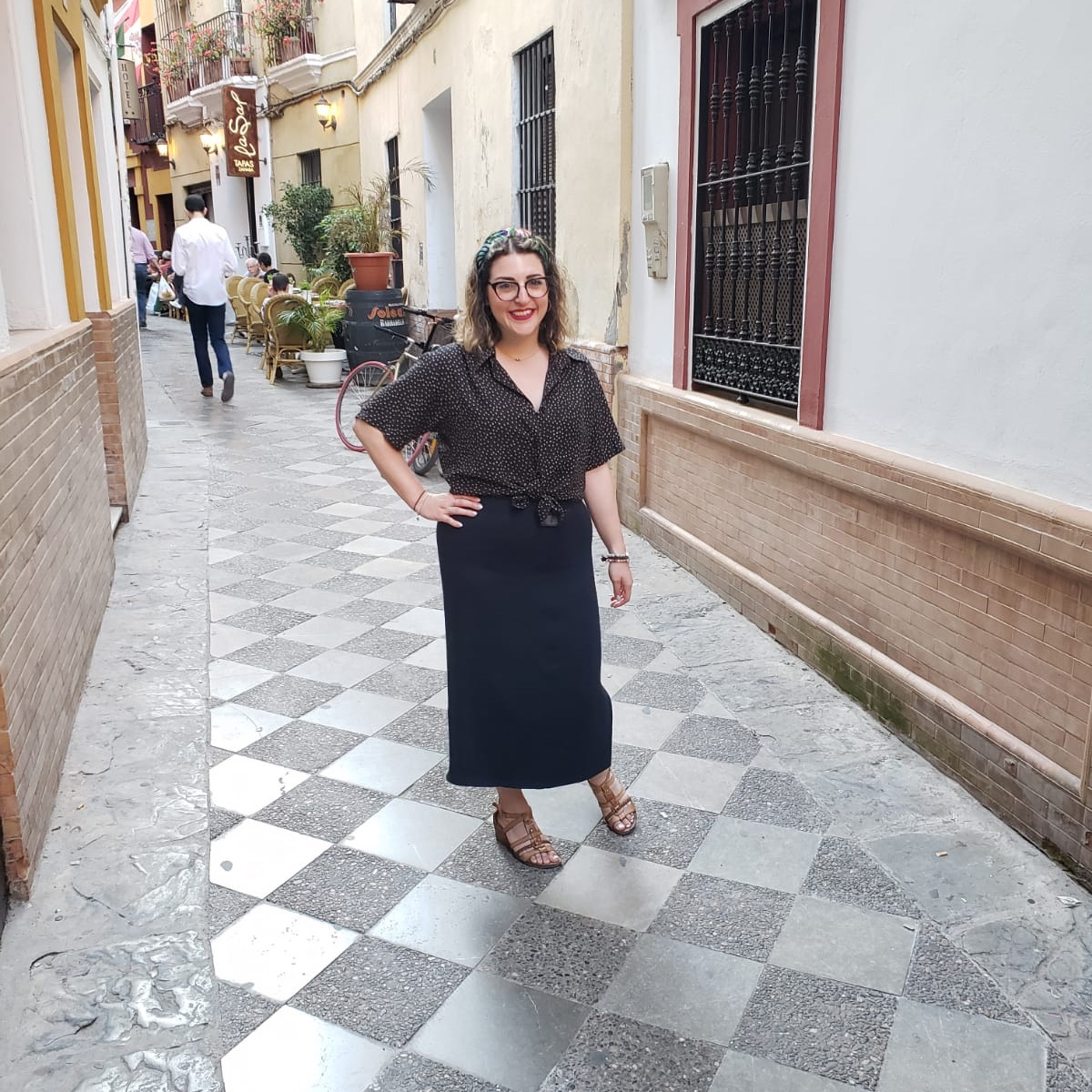Author Leviana Coccia stands in an alleyway in Sevilla, Spain. She is wearing brown wedged sandals, a long blue skirt, a polka dot blouse and a colourful headband. Photo courtesy of: Leviana Coccia.