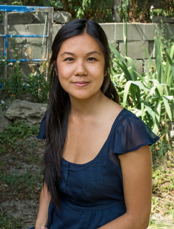 Andrea Kwan is a Registered Social Worker, Psychotherapist. In the image, Andrea is sitting in a green space, in the sunshine, wearing a navy blue blouse. Her hair is dark, straight, long and pulled to one side. This photo is by: Davide Burzotta.